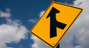yellow sign with directional arrow instructing a merging lane from the right in front of a sky with clouds background