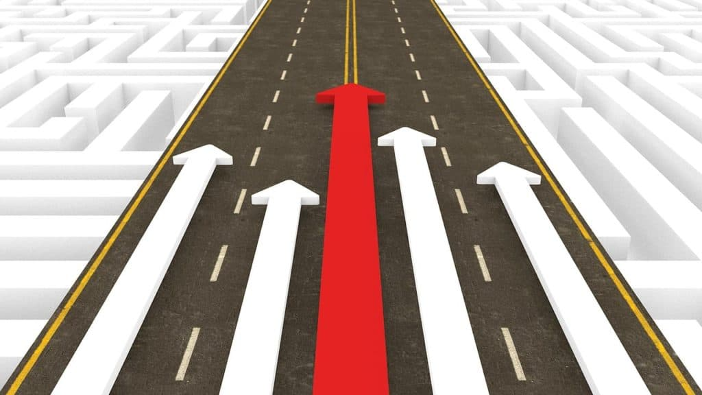 Roadway overlayed on a maze with five arrows pointing up the road. The center arrow is red, and taller than the others.