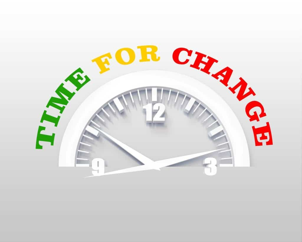 "Top half of a clock with the words, ""Time for Change"" around it on a gray background."