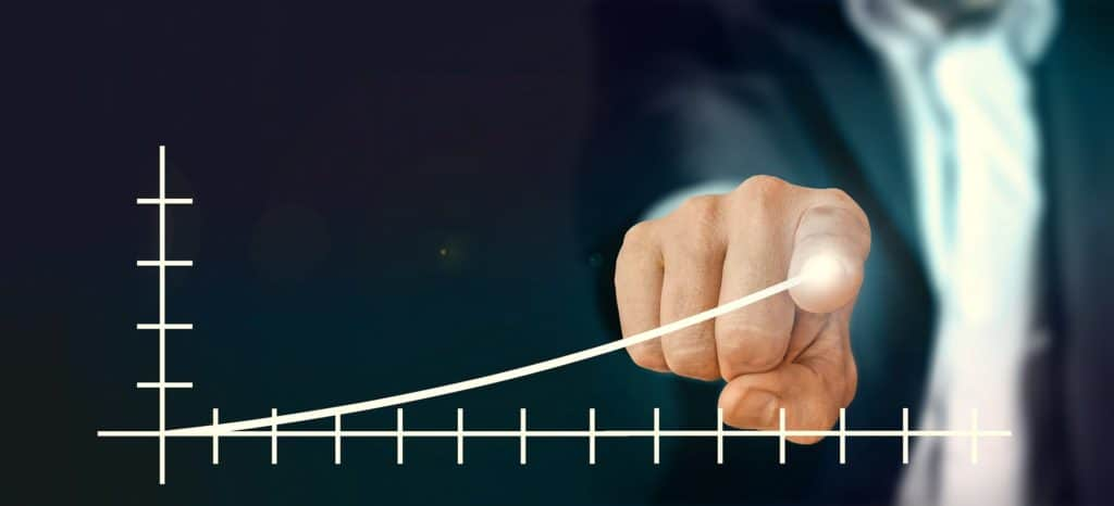 person in a suite pointing on the end of an illuminated x-y axis curve