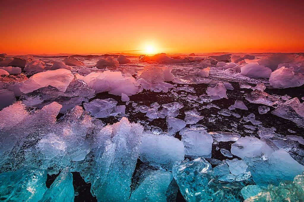 large broken pieces of ice with the son in the horizon with colors of blue purple orange and red