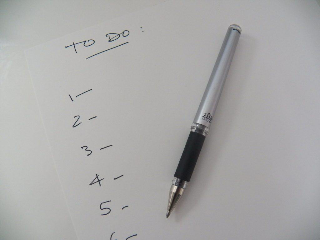 white paper with with a to do list number from one to six with a pen on the paper