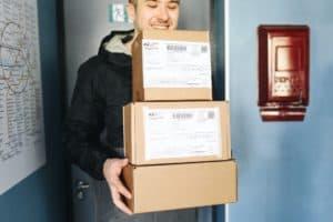 man in black jacket holding three cardboard boxes