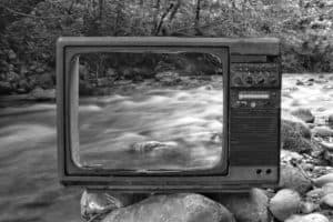 Black and white vintage old broken TV placed on stones near wild river flowing through forest